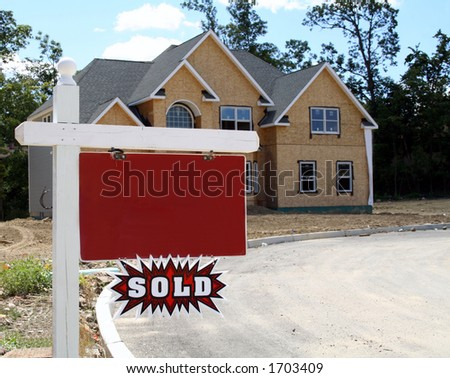 "New home being constructed with blank realtor sign and ""sold"" plaque"