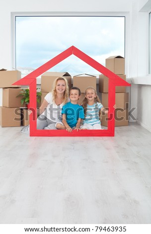 New home concept with happy people among cardboard boxes holding house shaped frame - stock photo