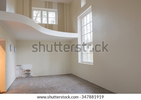 New home construction interior living room with unfinished tile wooden floors, big windows and balcony. The heating system also are partially unfinished. - stock photo