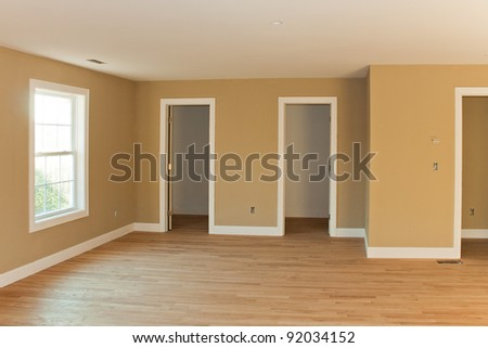 New home construction interior room with unfinished wood floors and twin closets.  The electrical and HVAC connections also are partially unfinished. - stock photo