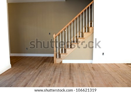 New home construction interior room with unfinished wood floors stairway and railings. Electrical and hvac connections are also partially unfinished and missing outlets. - stock photo