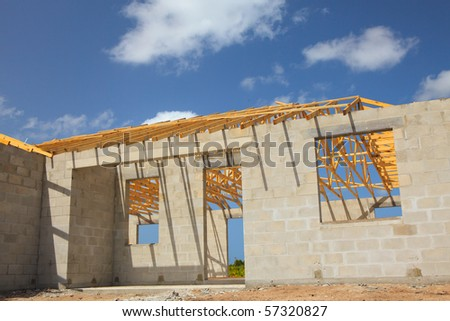 New home Construction of a cement block home with wooden roof trusses view from outside. - stock photo