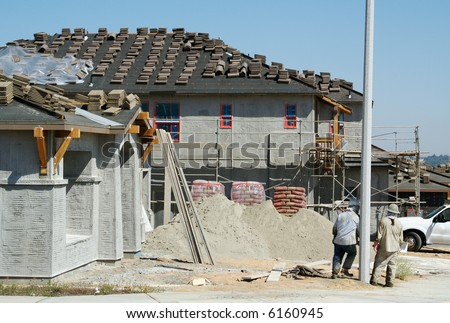 New Home Construction Site with Two Workers Resting. - stock photo