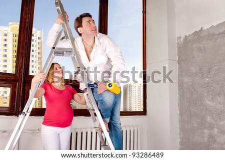 New home. Husband and the pregnant wife in the new house. - stock photo