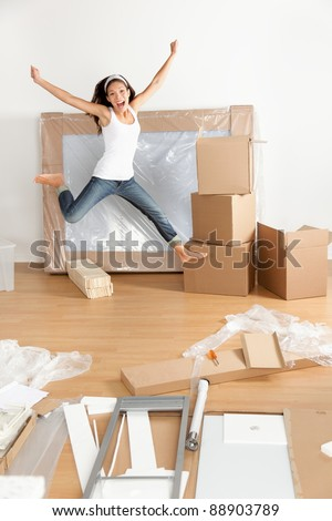 New home - moving woman excited and happy jumping of joy with moving boxes. Young Asian Caucasian woman. - stock photo