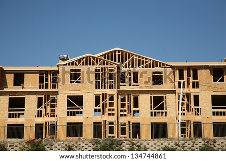 New Home or Condo Community Construction Site. New Homes being built with wood and other construction materials for new home buyers to live in and raise their families in Southern California. - stock photo