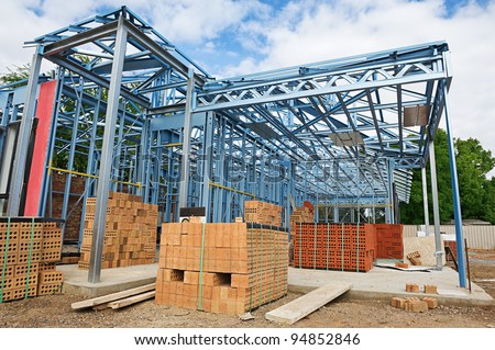 New home under construction using steel frames against a blue sky - stock photo