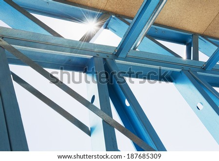 New home under construction using steel frames against a sunny sky. - stock photo
