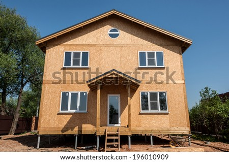 New house built from panels on blue sky background - stock photo