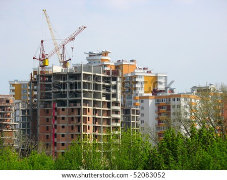 New house construction view with crane over blue sky background - stock photo