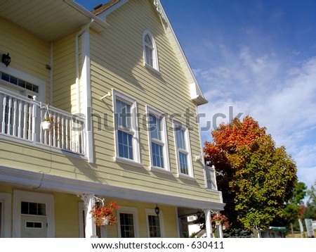 New house in fresh colors and fall tree.( good for real estate picture ) - stock photo