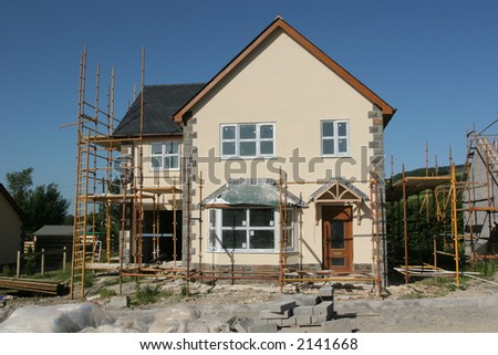 New house under construction with scaffolding, set against a blue sky. - stock photo