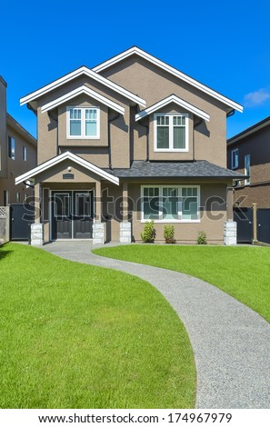 New house with concrete pathway over front yard lawn. Small family house in Vancouver, British Columbia.