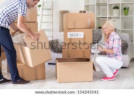 New house: Young couple moving box, unpacking - stock photo