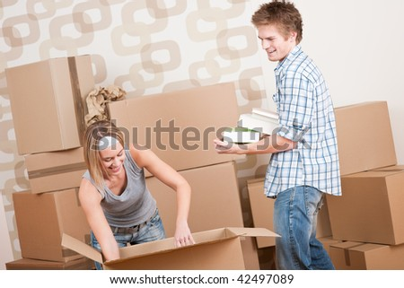 New house: Young couple with box in new home unpacking book