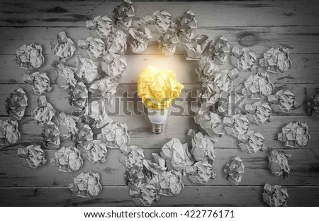 New idea concept with black and white crumpled office paper and light bulb - stock photo