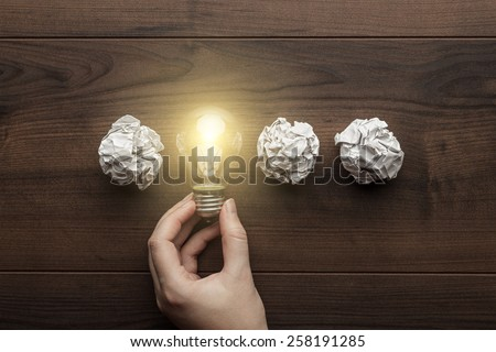 new idea concept with crumpled office paper, female hand holding light bulb - stock photo