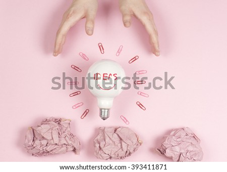 new idea concept with crumpled office paper, female hand holding light bulb. - stock photo