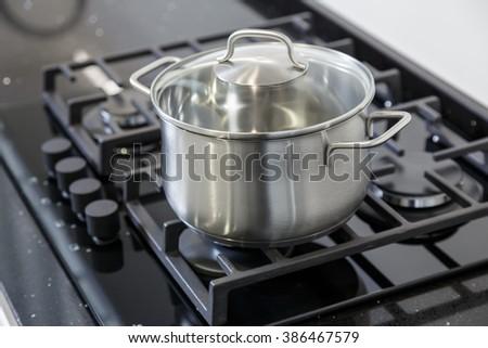 New iron pot on a black gas stove on a kitchen - stock photo