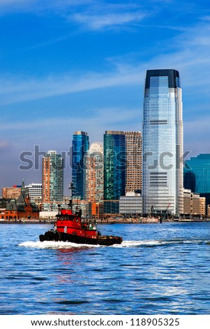 New Jersey skyline and waterfront viewed from the Hudson River with a red tugboat in the foreground. The city is Hoboken, across the water from lower Manhattan. - stock photo