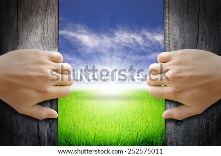 New Life concept. Hand opening an old wooden door and found a texts floating over green field and bright blue Sky Sunrise. - stock photo