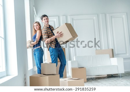 New life. Couple in love moving and keep a box in his hands and looking at the camera while a young and beautiful couple in love sitting on the couch in an empty apartment among boxes - stock photo