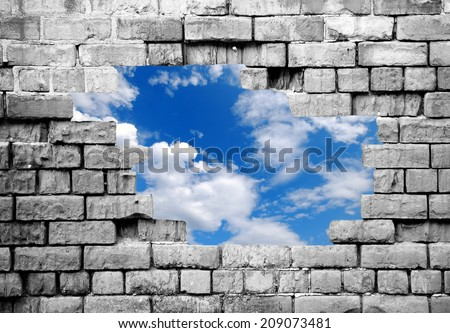 New life: Grey crumbling brick wall with cutout showing blue sky beyond - stock photo