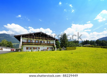 New lone house in a green field against blue sky over a tranquil mountain view. - stock photo