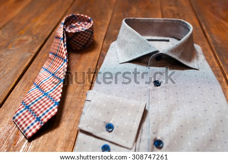 New men's checkered tie and shirt on a dark wooden background - stock photo