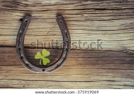New metal horseshoe with four leaf clover on old retro vintage aged wooden background Empty space for inscription or object Symbol of lucky