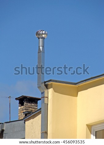 New metal ventilation chimney on the roof with rotor on top. - stock photo