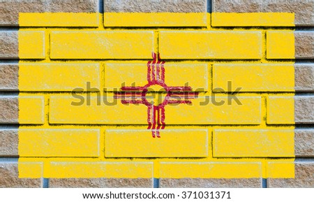 New Mexico state flag of America on brick wall - stock photo
