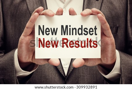 New Mindset New Results. Man holding a card with a message text  - stock photo