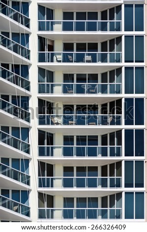 New Modern apartment house - this is a vertical, color photograph of a high rise, Miami Beach apartment building. The detailed shot shows the repetition of balconies. - stock photo