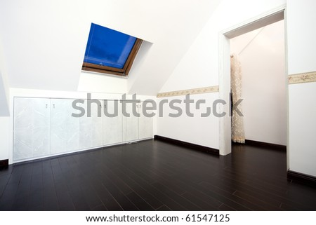 New modern attic room with a roof skylight window and wall cabinet - stock photo