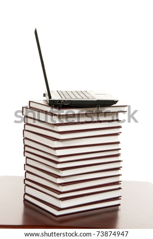 New modern black silver laptop on top of pile of  old educational books on a white background. - stock photo