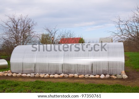 New modern  greenhouse at garden in spring - stock photo