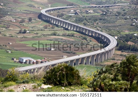 new modern highway winding among green valley, Segesta village, Sicily, Italy - stock photo