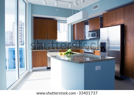 New modern kitchen interior with island in a condo apartment. Brightly lit, light blue walls, granite counter tops, stainless steel appliances. Lemons and fresh salad on the counter top. - stock photo
