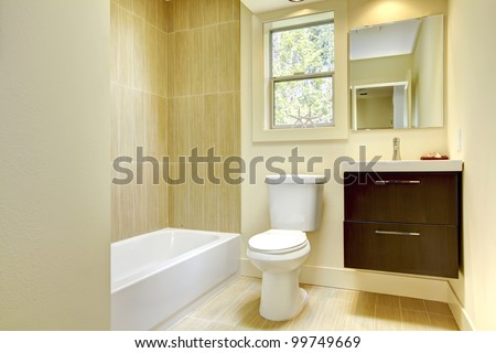 New modern yellow bathroom with beige tiles and brown cabinet. - stock photo
