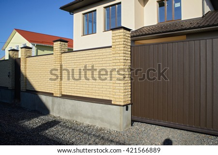 New modern yellow high metal fence in early spring - stock photo
