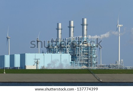 New multi-fuel power station (Nuon Magnum) that can run on gas, bio-mass and coal, and wind turbines in a harbor (Eemshaven, Groningen, The Netherlands). - stock photo
