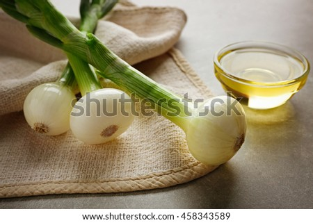 New onion with oil on grey background - stock photo