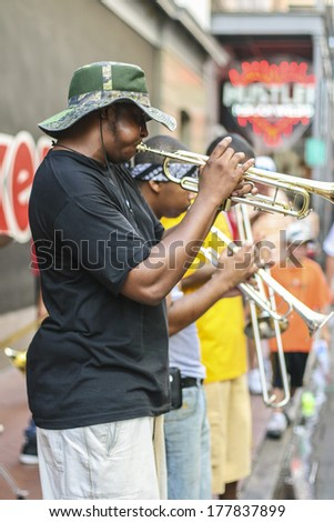 NEW ORLEANS - AUGUST 2, 2010: A group of young musicians perform on a sidewalk in the French Quarter. - stock photo