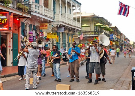 NEW ORLEANS - AUGUST 7: In New Orleans on Bourbon St. on August 7, 2013, a jazz band plays jazz melodies in the street for donations from the tourists and locals passing by on this hot summer evening. - stock photo