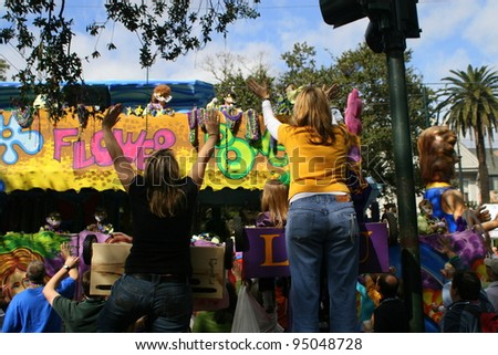 NEW ORLEANS - FEBRUARY 2: People on the float threw doubloons and beads to the crowd in Mardi Gras parade. February 2, 2008 in New Orleans, Louisiana. - stock photo
