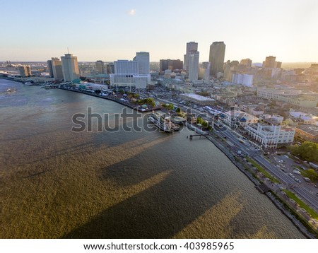NEW ORLEANS, LOUISIANA  - APRIL 10, 2016: Cityscape of New Orleans during the French Quarter Festival. Stages and people, Mississippi river in background.
