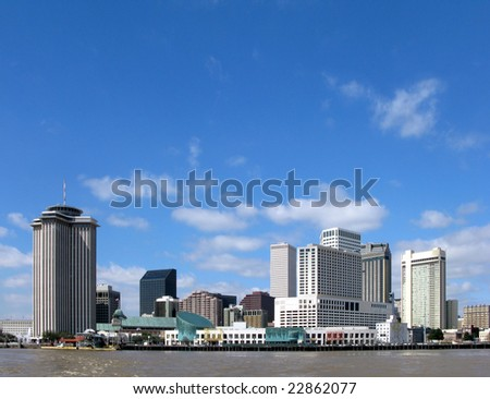 New Orleans Louisiana downtown skyline cityscape of the hotel district and commercial waterfront across the Mississippi River from Algiers on a sunny day with blue sky - stock photo