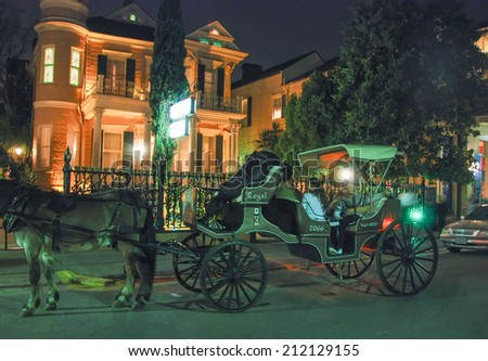 NEW ORLEANS - MARCH 7, 2009: Tourists on horse carriage at night. Almost 9 million people visit New Orleans every year. - stock photo