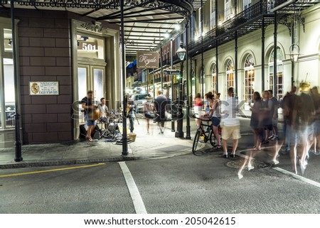 NEW ORLEANS, USA - JULY 14, 2013: people in the French Quarter with bands playing Jazz in New Orleans, USA. Tourism provides a much needed source of revenue after the devastation of Hurricane Katrina. - stock photo